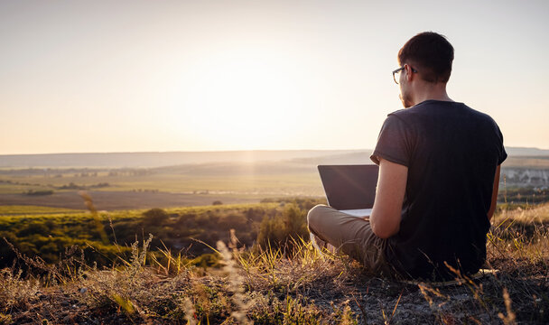 man with laptop sitting on the edge of a mountain with stunning views of the valley