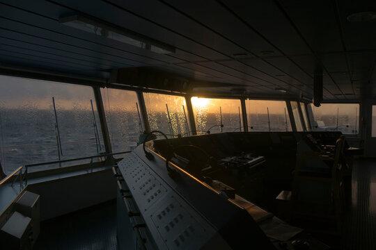washing windows on the navigation bridge at sunset