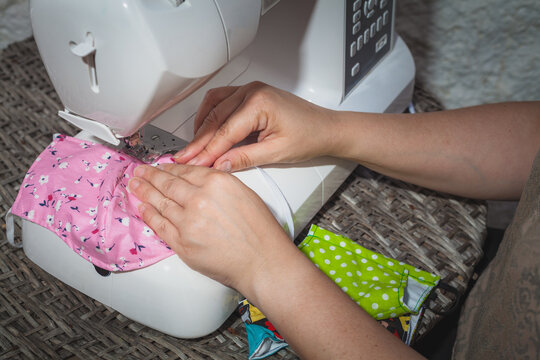 hands of a seamstress sewing with a sewing machine a face mask artisan pink
