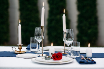 Table setting, wineglasses, candles and flower