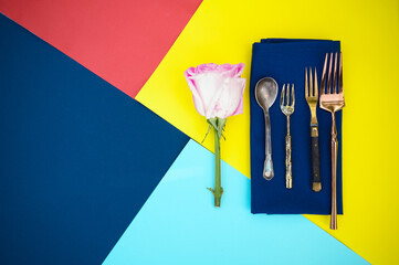 Table setting, flower and silverware on napkin