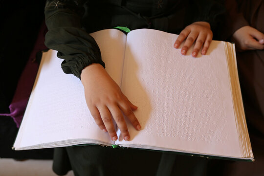 Blind Palestinian girl Shams Abu Shahma reads a braille version of the Koran inside her family home in the Khan Younis in the southern Gaza Strip