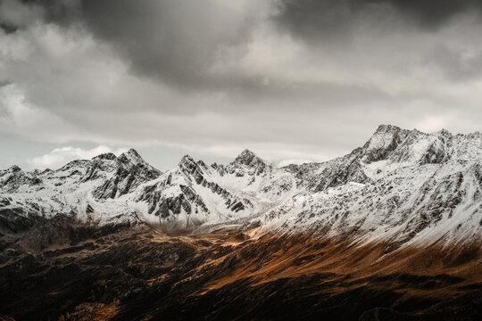 Bilich von der Nufenenpass Strasse auf die schweizer Alpen mit schneebedeckten Gipfeln und bewölktem Himmel. Nufenenpass