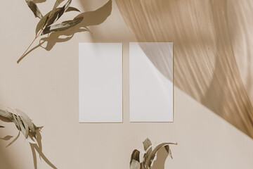 Photo sur Plexiglas Pays d Afrique Blank paper sheet cards with mockup copy space, wooden tray and dry leaves with sunlight shadow on beige background. Minimal business brand template. Flat lay, top view