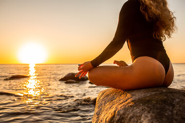 Hand of a woman meditating in a yoga lotus pose on the beach at sunset. Girl sitting on a warm rock.