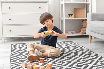 Little boy with autistic disorder playing with cubes at home