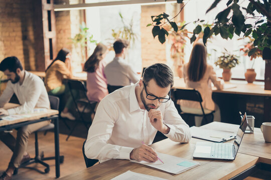 Nice confident professional focused guy people financier agent broker insurance consulting document researching at modern industrial loft brick open space style interior workplace workstation