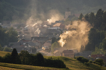 mountain village in the valley suffocating with smoke and smog from wood and coal-fired stoves
