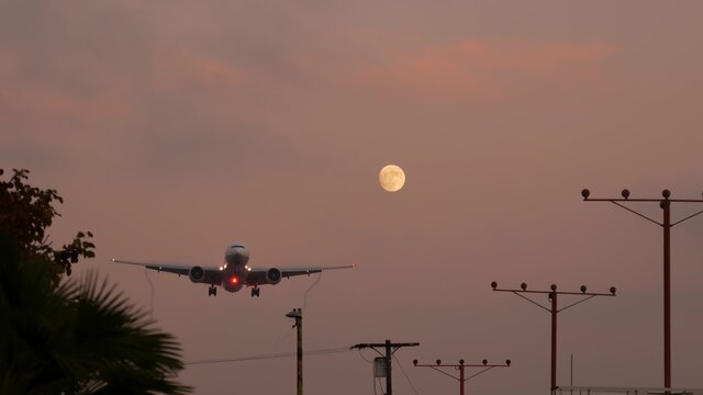 Airplane landing in LAX airport at sunset, Los Angeles, California USA. Passenger flight or cargo plane silhouette, dramatic cloudscape. Aircraft arrival to airfield. International transport flying