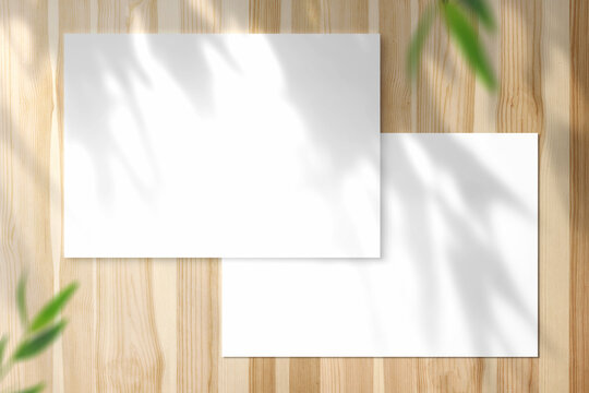 Two blank horizontal A5 Poster on shiny wooden desk