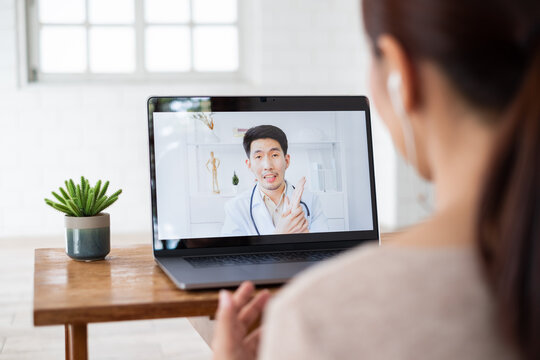 Asian woman talking with doctor via computer laptop virtual video call or video conference, telehealth and telemedicine concept