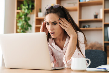 Image of annoyed adult businesswoman with headache using laptop