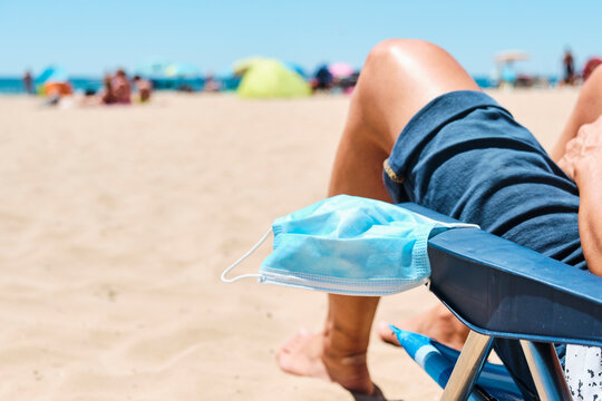 mask and man sitting in a deck chair on the beach