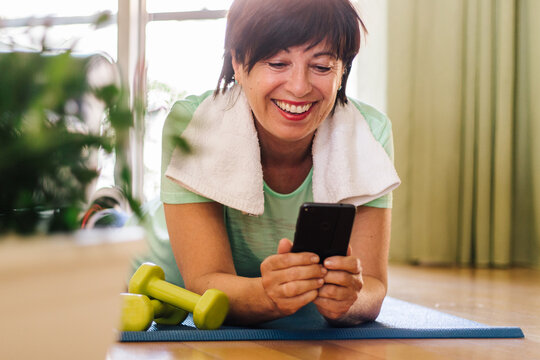 Beautiful brunette older woman training gym at home holding smartphone.