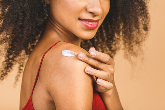 Young african american woman with bare shoulders standing isolated on beige background applying cream on body smiling joyful.