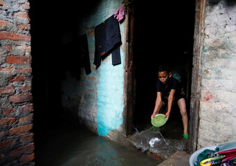 A boy uses a plate to clear water entering his house as the river overflows due to incessant rainfall at a slum along the bank of Bagmati River in Kathmandu