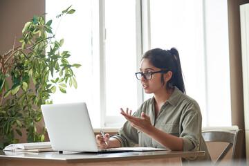 Indian woman online tutor remote teacher wearing glasses speaking to webcam chat explaining online...