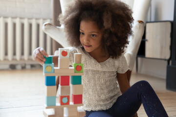 Photo sur Plexiglas Akt Playful little african American girl sit on warm floor at home play construct tower with wooden bricks, cute small biracial child have fun enjoy game with blocks or cubes, education, learning concept