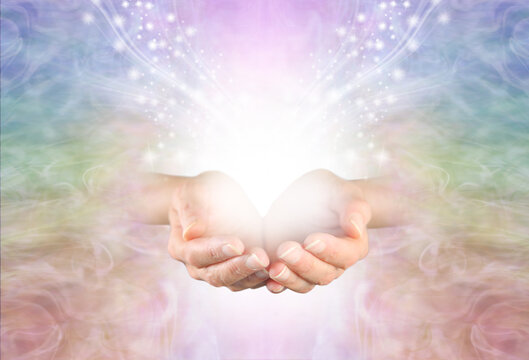 Healing is a magical experience  - female hands with with white light and a flow of sparkles against a pale rainbow coloured background with room for messages