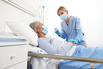 nurse with thermometer measures fever on elderly woman patient lying in the hospital room bed, wearing protective gloves and medical surgical mask, coronavirus covid 19 protection concept