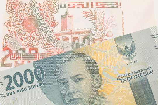 A macro image of a grey two thousand Indonesian rupiah bank note paired up with a beige 200 Algerian dinar bank note.  Shot close up in macro.