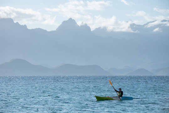 One woman paddling on a seat on top kayak close to the shore of Carmen Island in Loreto, Baja California, Mexico.