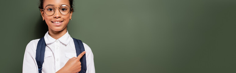 smiling african american schoolgirl pointing at empty green chalkboard, panoramic shot