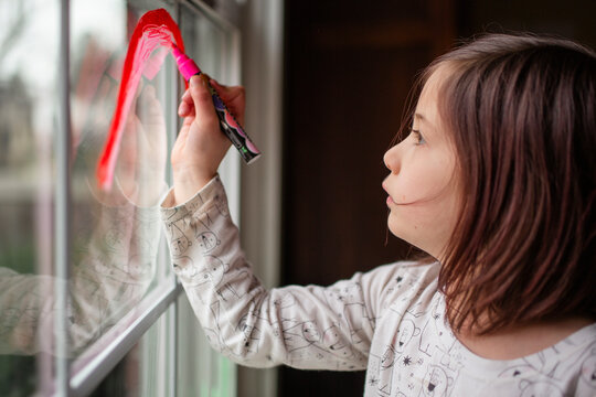 A small serious child draws a rainbow on a window with red marker