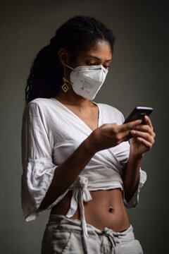 Woman with face mask using a smartphone