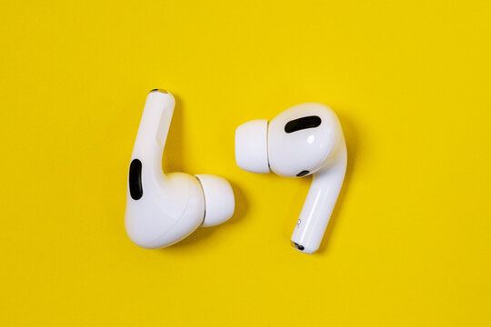 Rostov, Russia - July 06, 2020: Apple AirPods Pro on a yellow background. Silent wireless headphones close up..