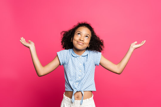smiling cute curly african american kid showing shrug gesture isolated on pink