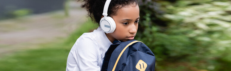 sad african american schoolgirl with backpack and headphones sitting outside, panoramic shot