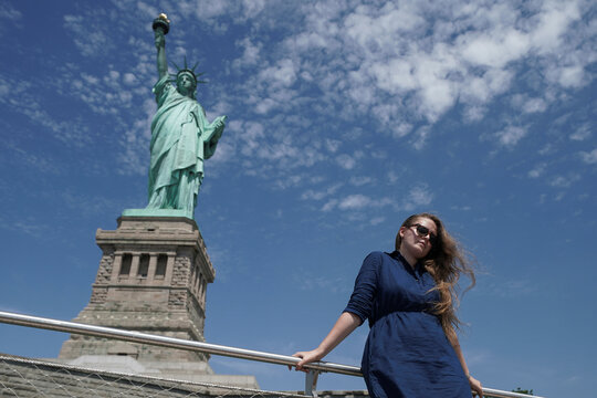 A person poses for a photo at the Statue of Liberty as New York enters Phase 4 of reopening following the outbreak of the coronavirus disease (COVID-19) in New York City