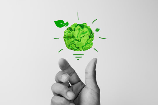 Corporate Social Responsibility (CSR), eco-friendly business concepts with businessman hand holding crumpled green paper light bulb
