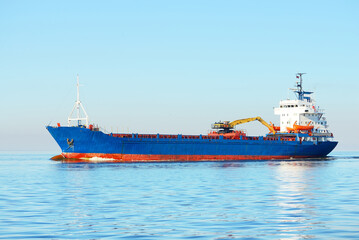 Large blue bulk carrier (ship) sailing in the Baltic sea to Riga port, Latvia. A view from the yacht. Global communications, logistics, industry, freight transportation