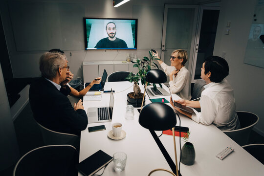 Male and female colleagues discussing with businessman through video call in board room during meeting late at night