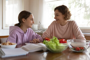 Happy mother and teenager daughter chatting, sitting at table in modern kitchen, smiling teen schoolgirl studying, working on school assignments, homework, mum cooking salad, preparing dinner