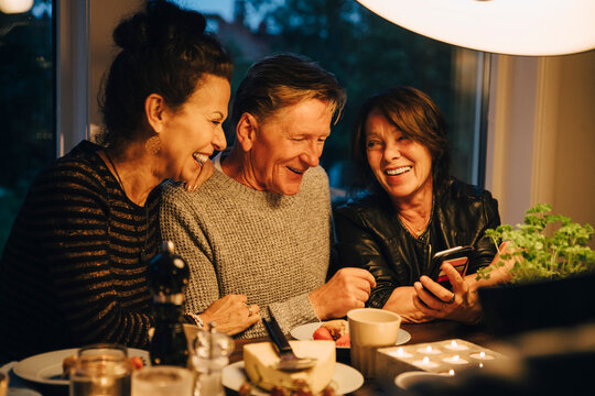 Smiling senior woman sharing smart phone with friends while sitting at dining table during dinner party