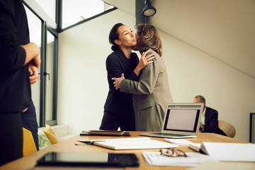 Female lawyers embracing while greeting in office during meeting