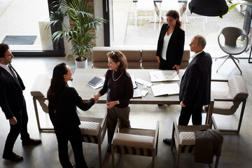 High angle view of female financial advisor greeting businesswoman while colleagues standing in office during meeting