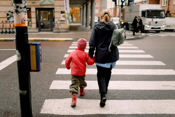 Rear view of grandmother holding hand of grandson while crossing street in city