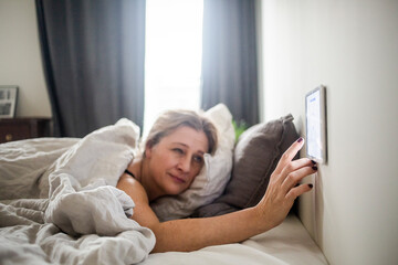 Woman using digital tablet mounted on wall while lying on bed at smart home