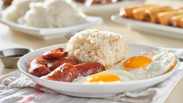 filipino silog breakfast with garlic fried rice, longsilog, and two sunny side up eggs