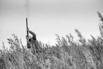 Black and white image of a gun firing at a pheasant flying overhead