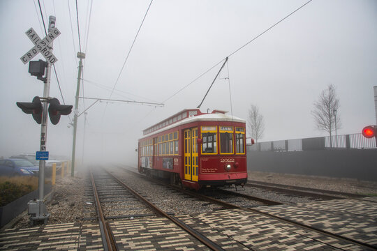 Street car emerging from dense morning fog in the French Quarter of New Orleans