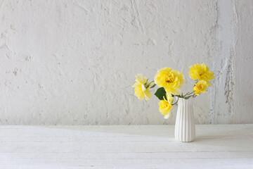Photo sur Plexiglas Nature yellow roses in white vase on background white wall