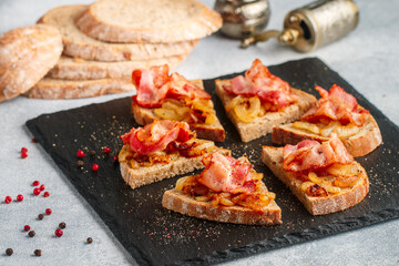 Delicious whole-grain bread sandwiches with fried onions, bacon and freshly ground pepper. Gourmet appetizer. Selective focus