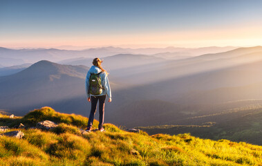 Obraz Beautiful mountains in fog and standing young woman with backpack on the peak at sunset in summer. Landscape with sporty girl, green grass, forest, hills , blue sky with sunbeams. Travel and tourism - fototapety do salonu