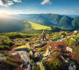 Beautiful mountains and standing young woman with backpack on the green stones at sunset in summer. Landscape with sporty girl on the mountain peak, forest, hills , blue sky with clouds and sunbeams