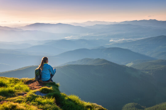 Young woman with backpack sitting on the mountain peak and beautiful mountains in fog at sunset in summer. Landscape with sporty girl, green grass, forest, hills , sky, sunbeams. Travel and tourism